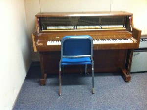 a piano with a blue chair