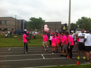 Runners from John Paul Secondary School at the start of the track with pink shirts and balloons