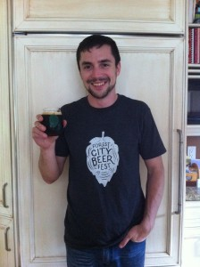 "Founder of the Forest City Beer Fest, Aaron Brown, holding a glass of beer with ""Forest City Beer Fest"" on the a green outline of a leaf. His navy t-shirt also has the logo, but the leaf is filled in white."