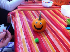 A tiny pumpkin with googly eyes and a smile painted on