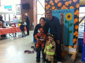 A woman and a man with a young boy dressed as a firefighter, and a baby dressed as a tiger