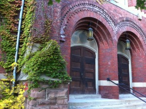 A red brick wall with a door, part of MCC London