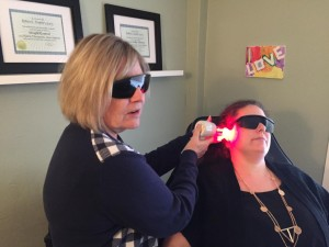 Deb Taylor, Owner of London Laser and Hypnotherapy Centre, treating a smoking patient with her laser.